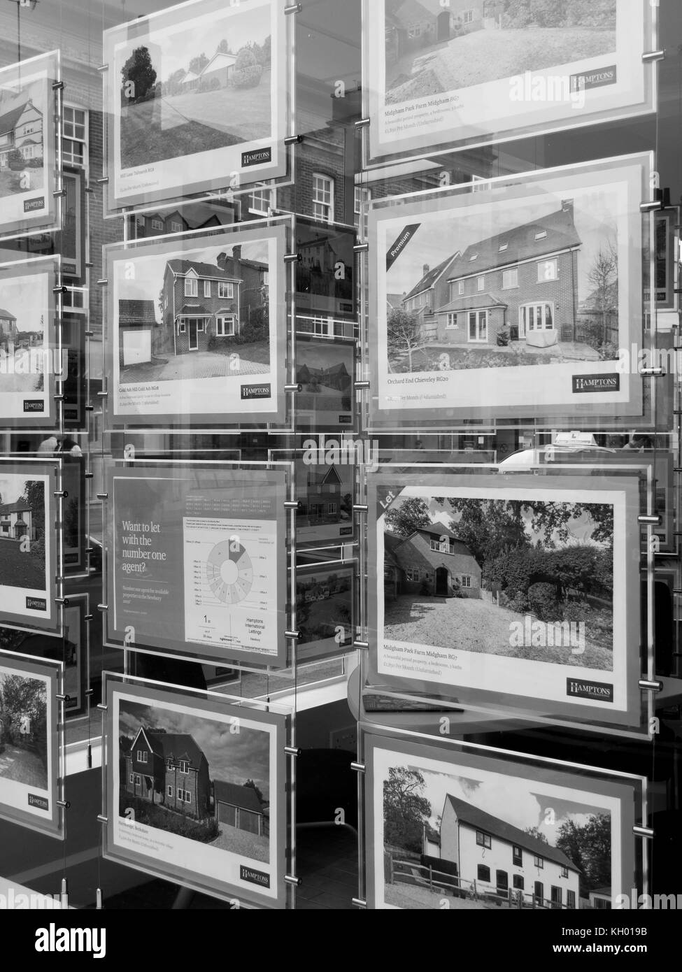 Residential properties for sale displayed in estate agents window - Stock Image