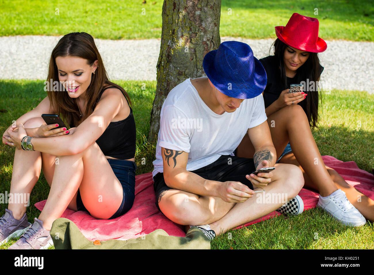 Friends with smartphones under tree - Stock Image
