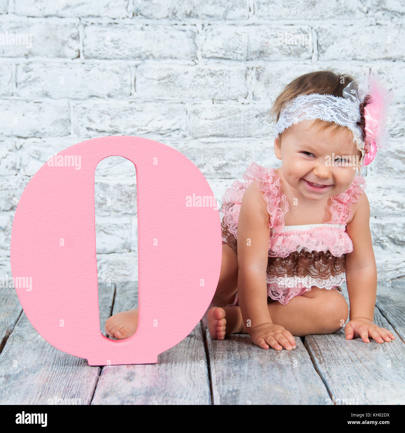21e813665 Beautiful and cute girl in a pink dress with the letter O. Emotional girl