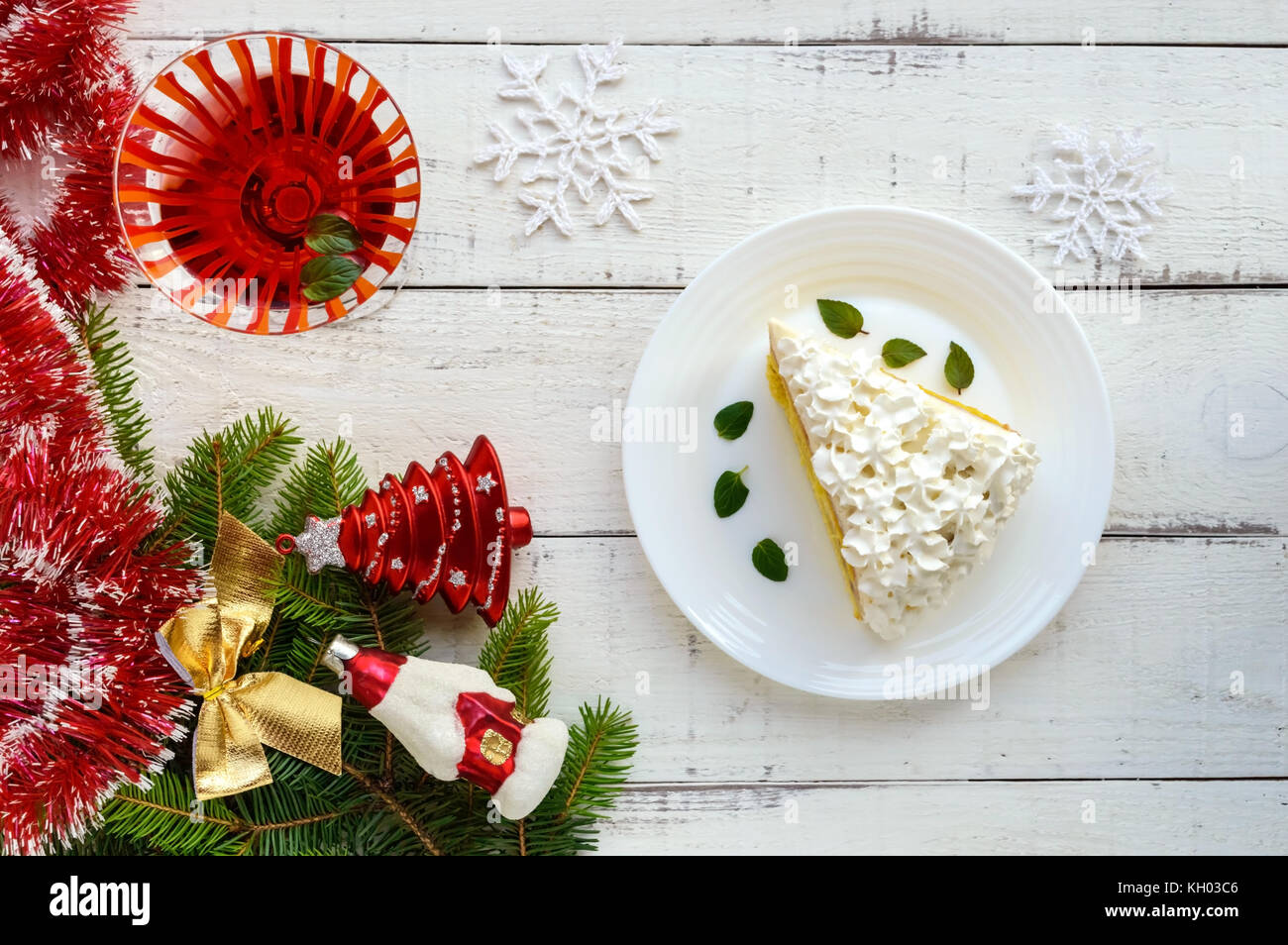 A large piece of delicate sponge cake decorating air cream. Glass with a cocktail. Festive dessert on a white background. - Stock Image