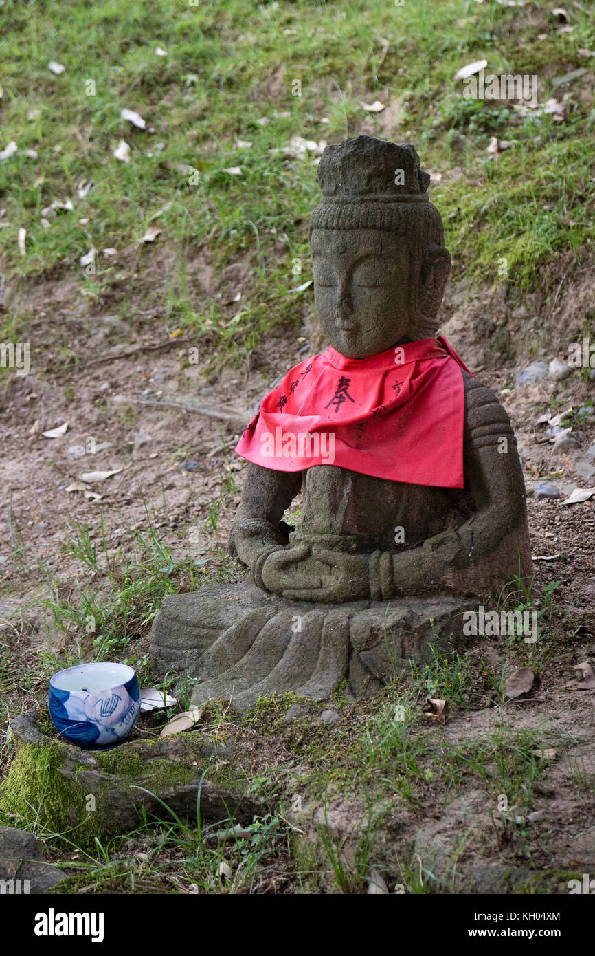 Nara - Japan, May 30, 2017: Traditional stone carved Jizo with red skirt honored and respected with a cup of water - Stock Image