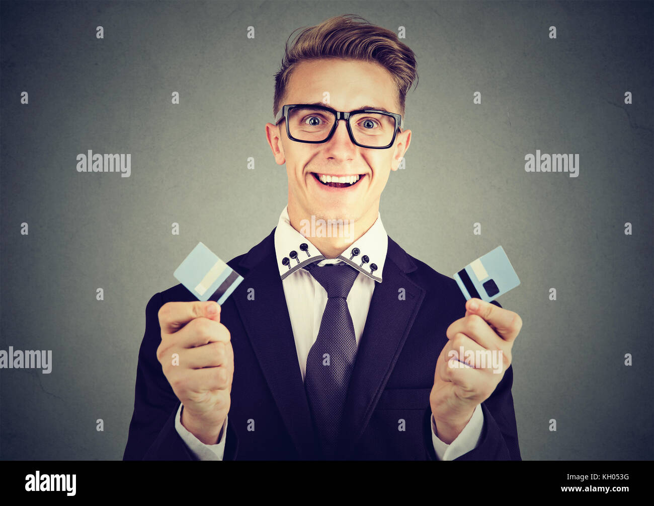 Happy debt free business man holding a credit card cut in two pieces - Stock Image