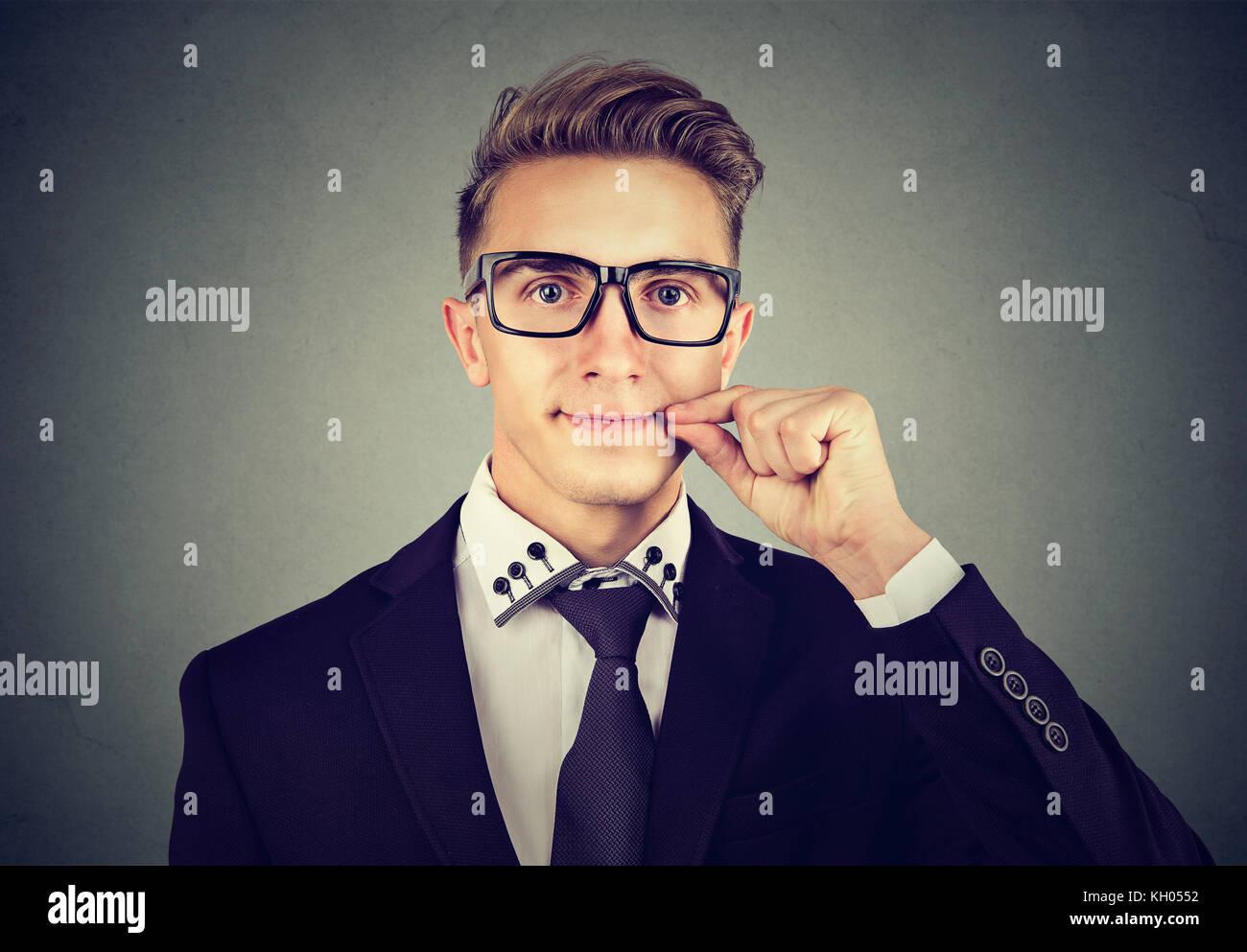 Keep a secret, man zipping his mouth shut. Quiet concept - Stock Image