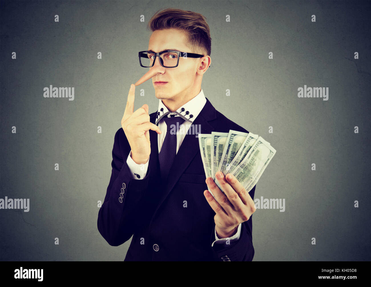Financial fraud concept. Liar young business man in suit and glasses with dollar cash - Stock Image