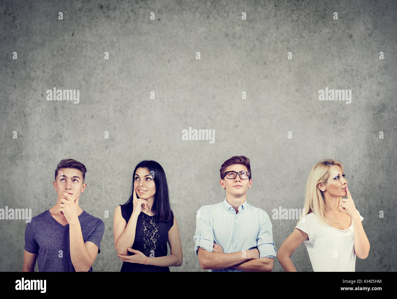 Portrait of two men and two women thinking hard looking up while standing near a concrete wall. - Stock Image