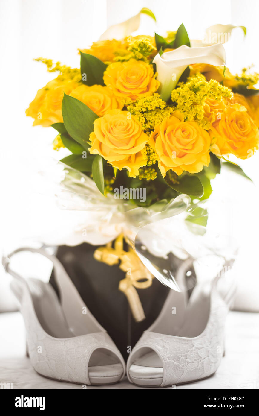 Yellow Roses With White Lilies And Bridal Shoe Arrangement Stock