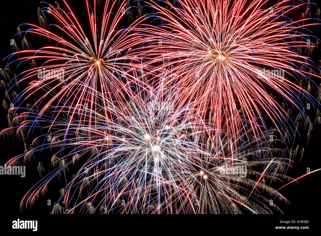 Bright festive background with beautiful colored fireworks, salute on the background of the black sky - Stock Image