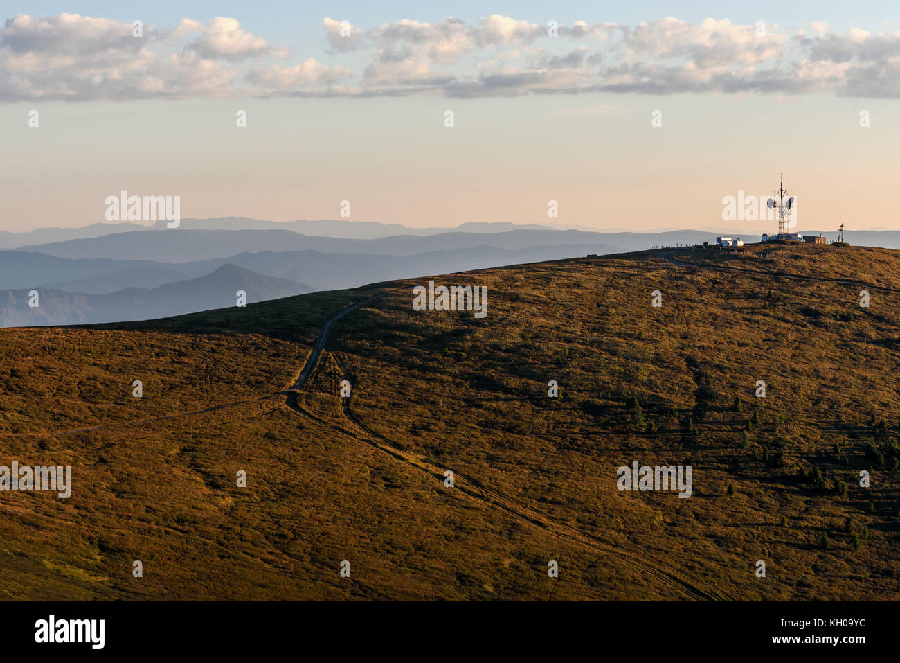 Scenic view with the repeater and telecommunications tower on top of a mountain road and trees at sunrise - Stock Image
