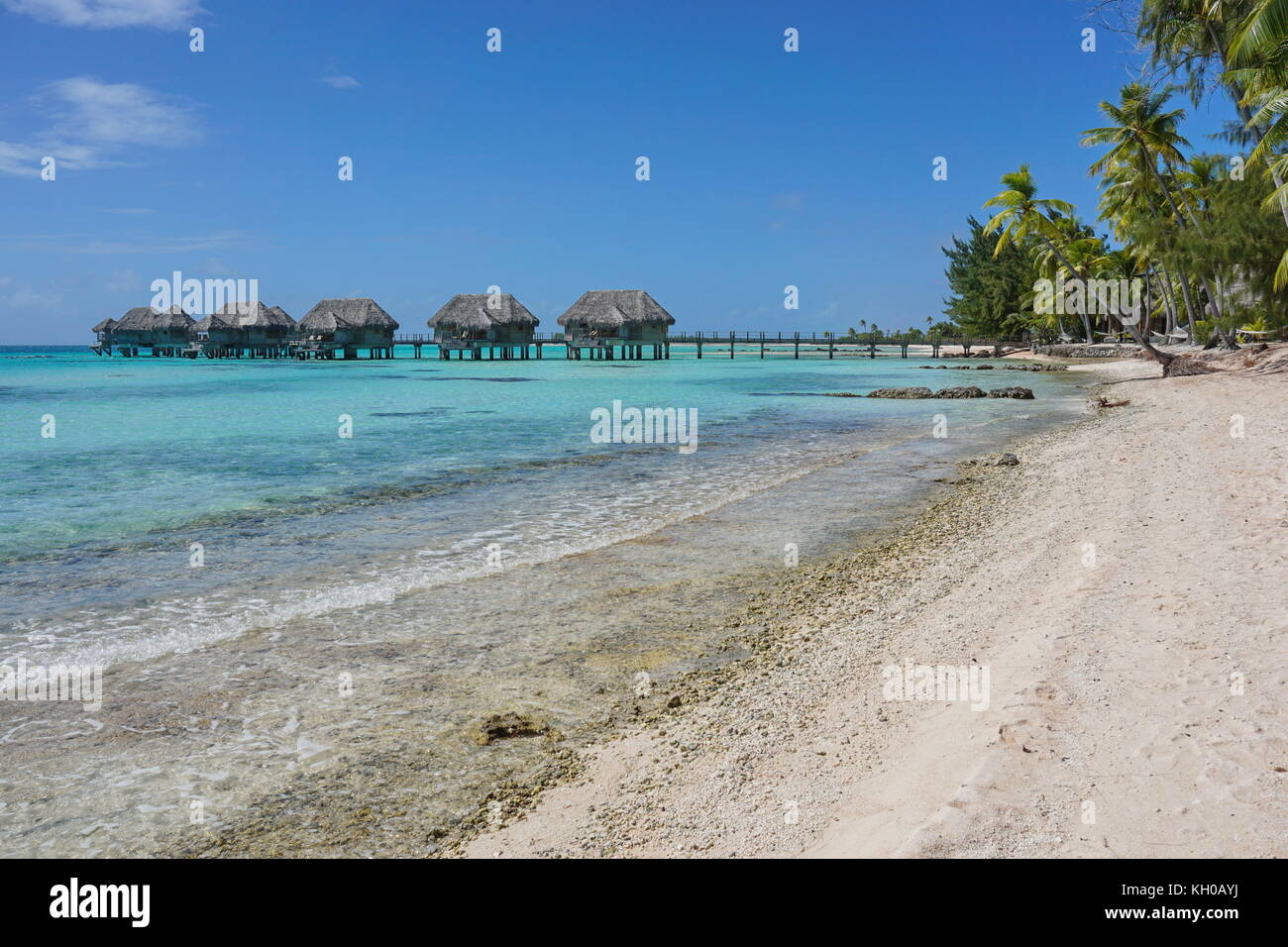 Tropical sea shore with bungalows over the water in the lagoon, Tikehau atoll, Tuamotus, French Polynesia, south - Stock Image