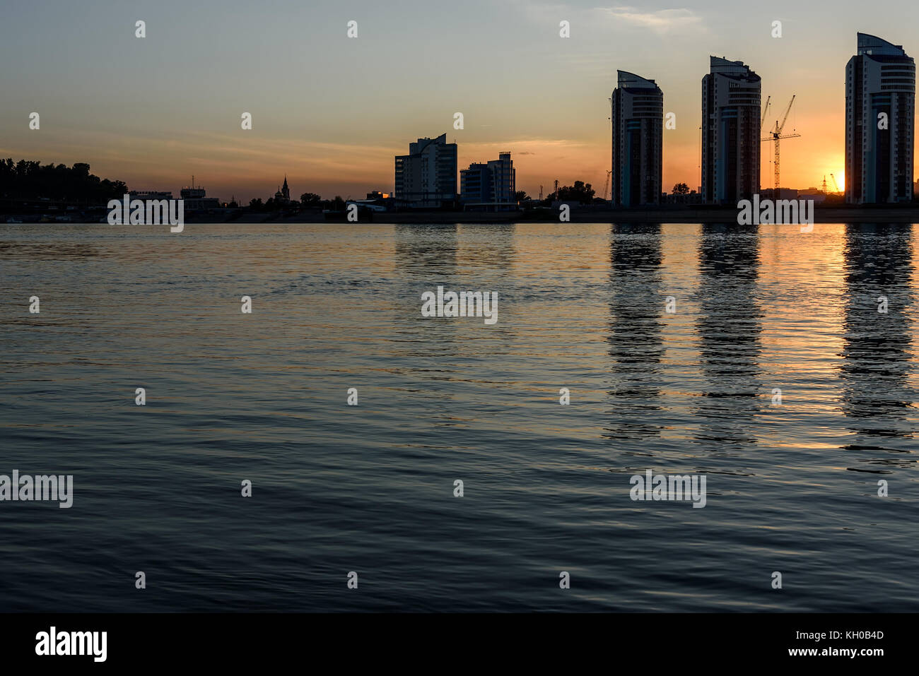 The picturesque landscape of the night city and the river with the reflections of tall houses on the water against - Stock Image