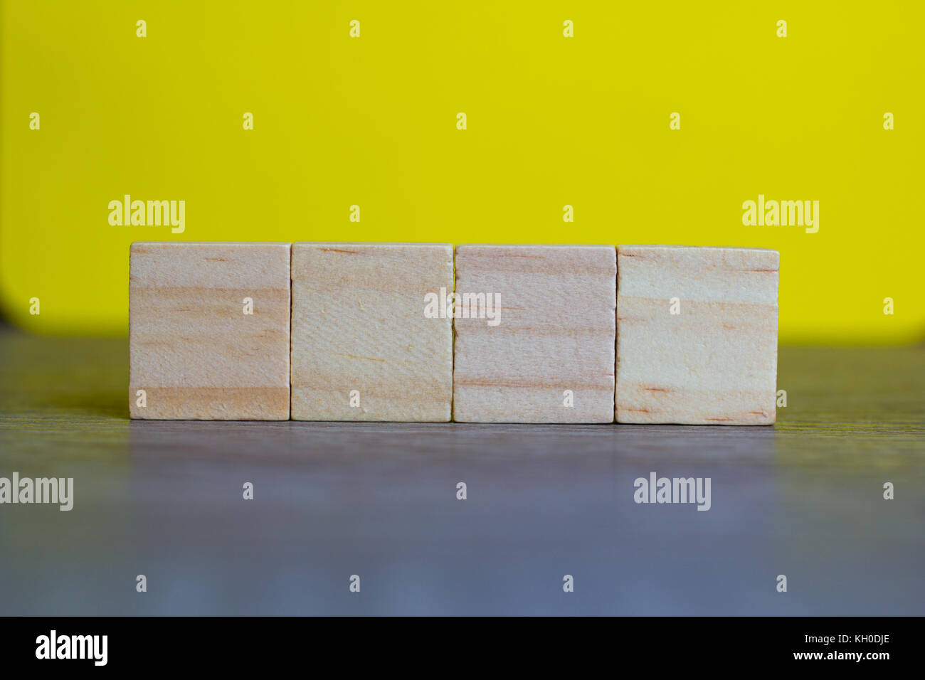 Four Empty Wood Cubes against yellow background - Stock Image