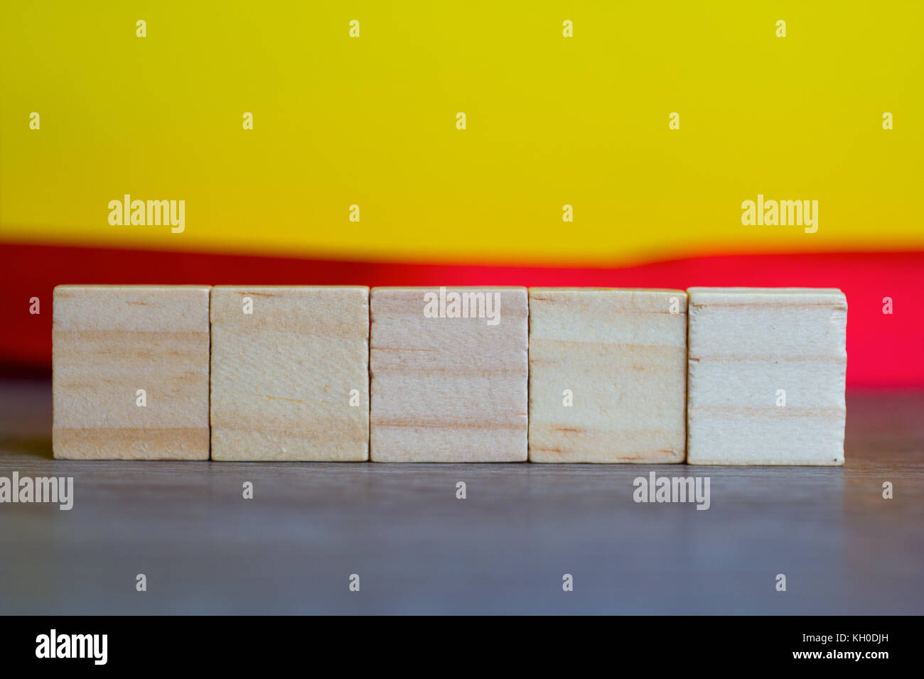 Five Empty Wood Cubes against yellow background - Stock Image