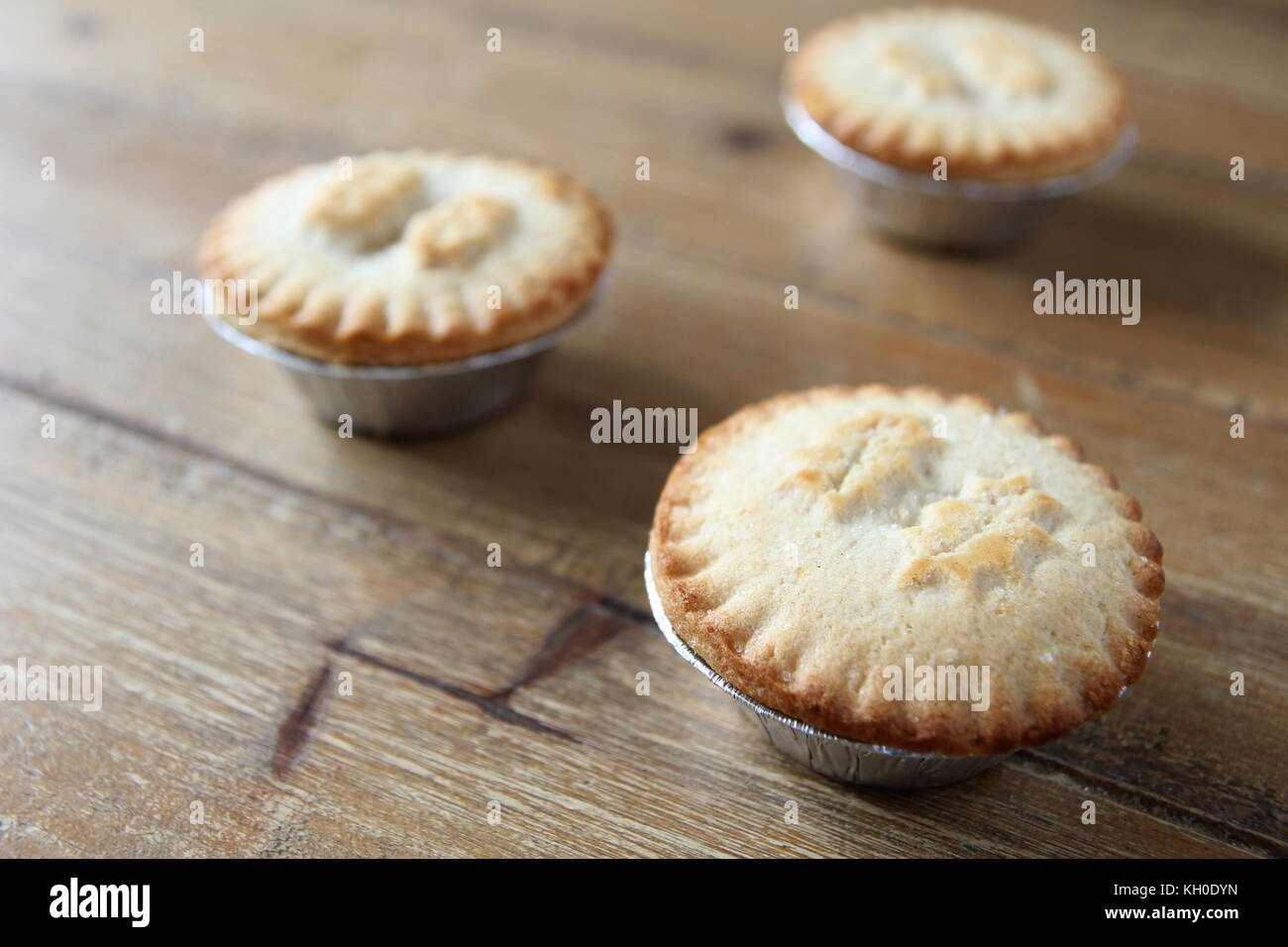 Close up shot of three mince pies in foil cases, traditional Christmas dessert - Stock Image