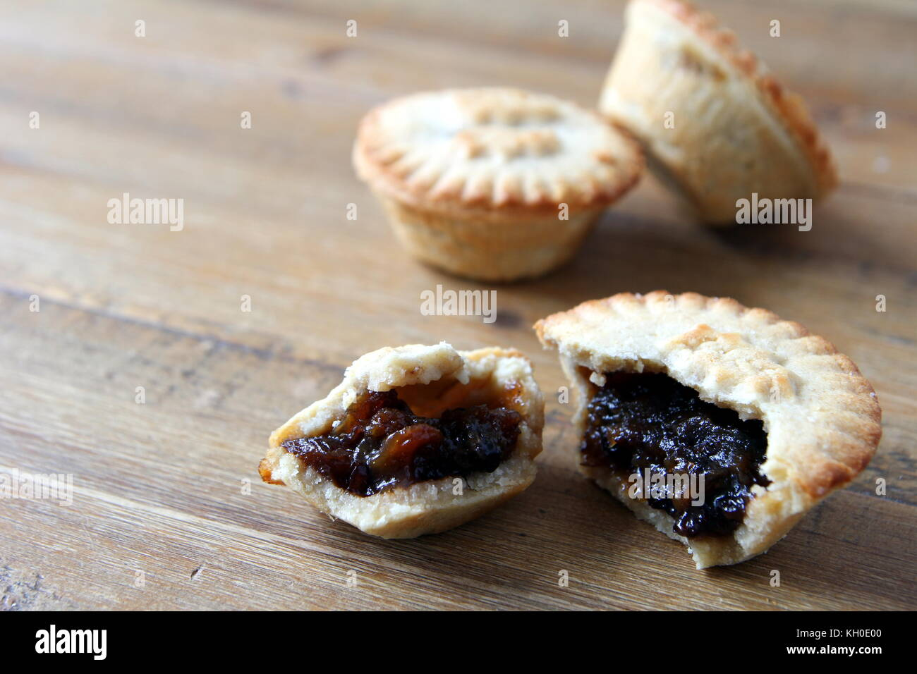 Selection of several mince pies, some broken open or partly eaten. A traditional festive Christmas dessert or pudding. - Stock Image