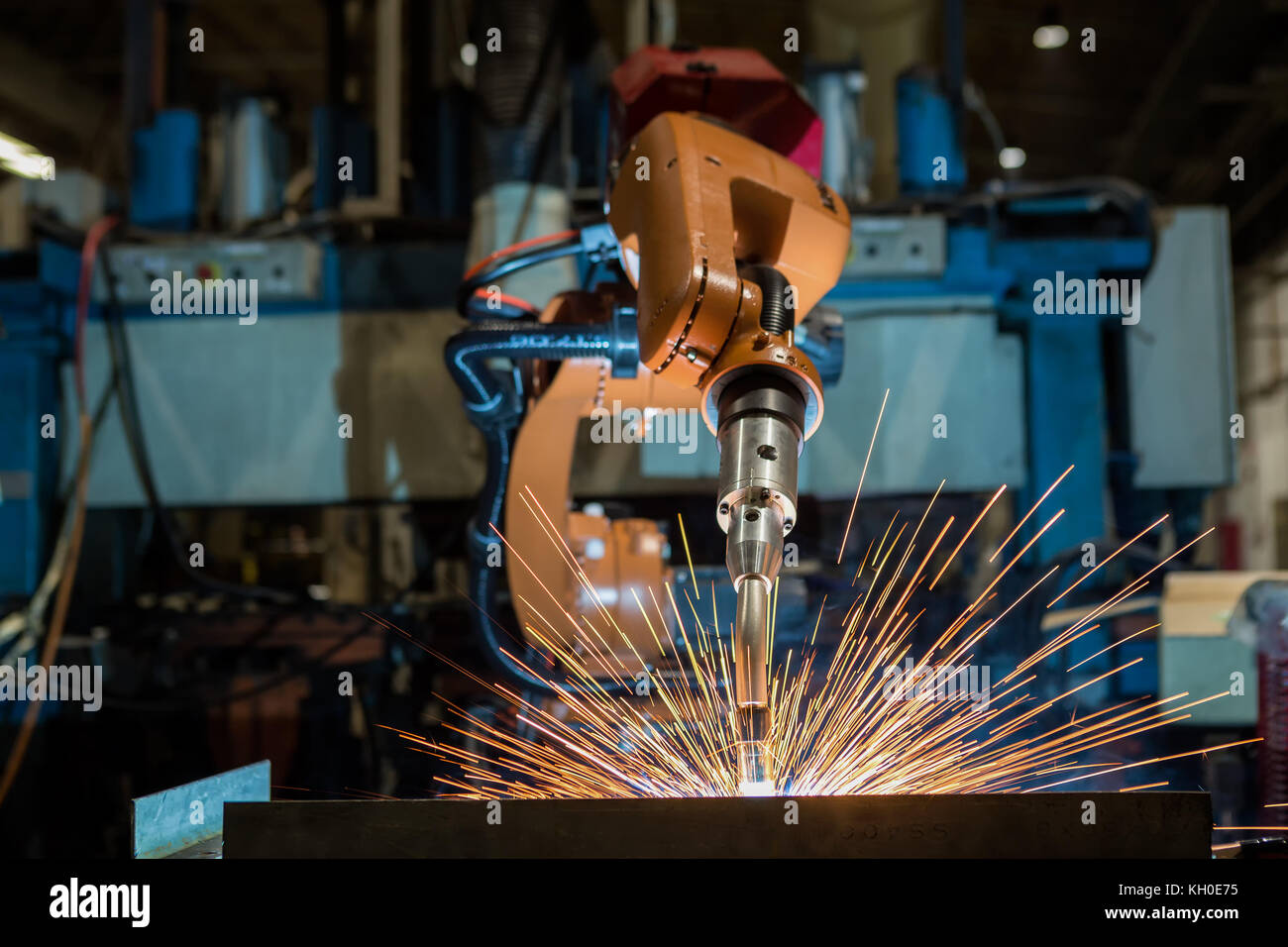 Orange robot is welding in car factory - Stock Image