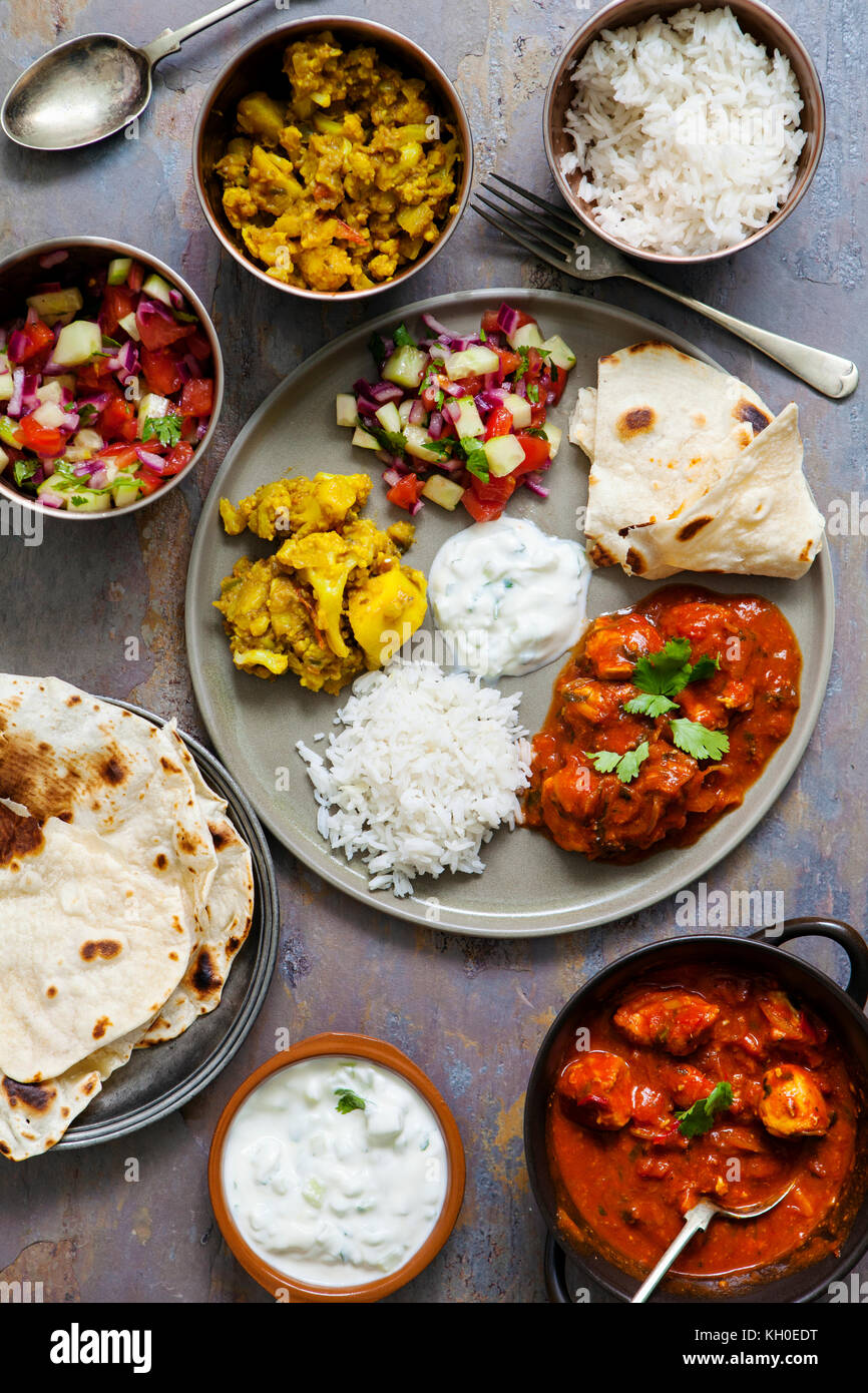 Indian meal with chicken tikka masala, aloo gobi, salad, rice and flat bread - Stock Image