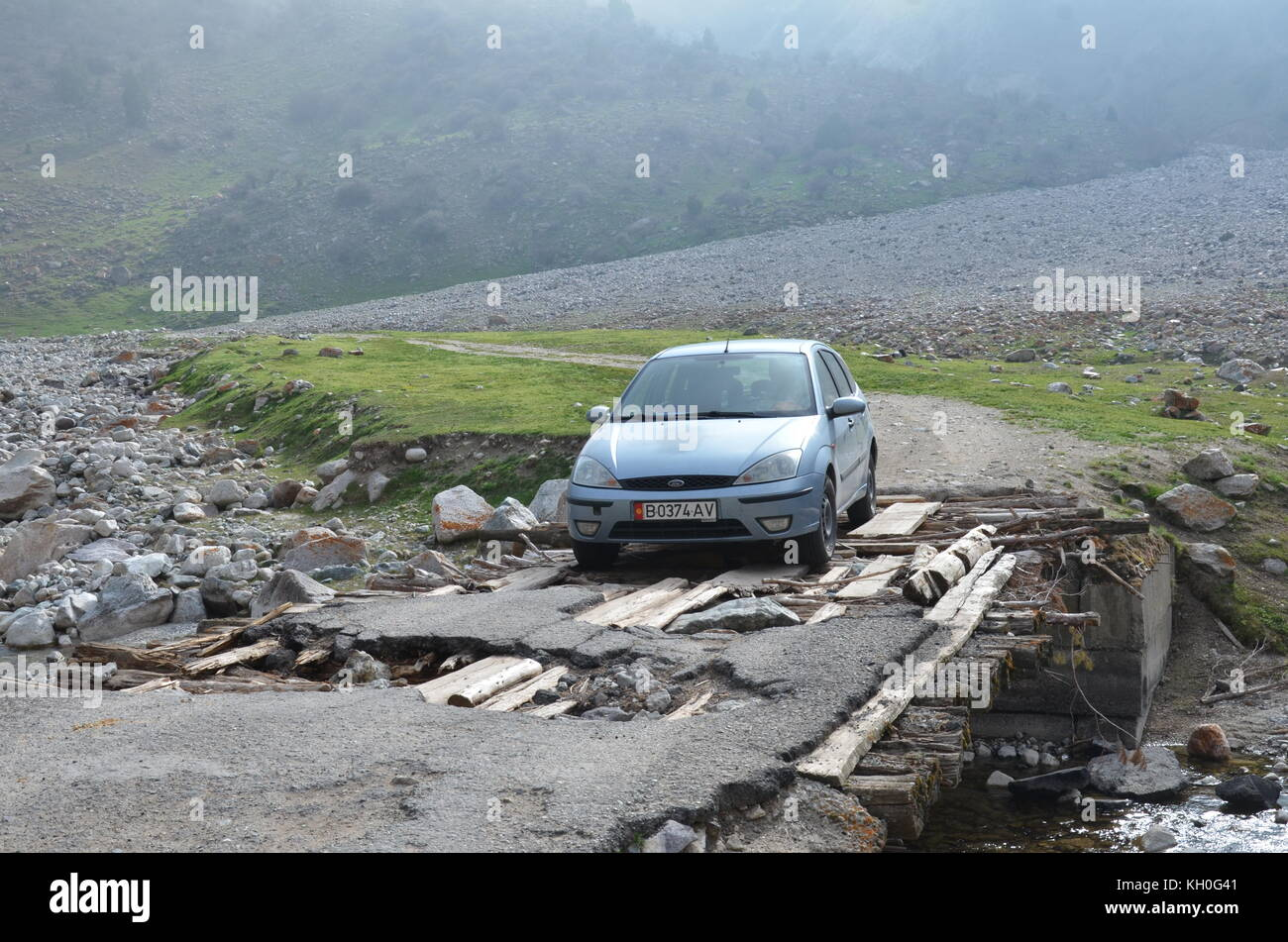 A car tries to drive over a shaky unstable wooden bridge in the middle of nowhere in Kyrgystan, Asia. - Stock Image