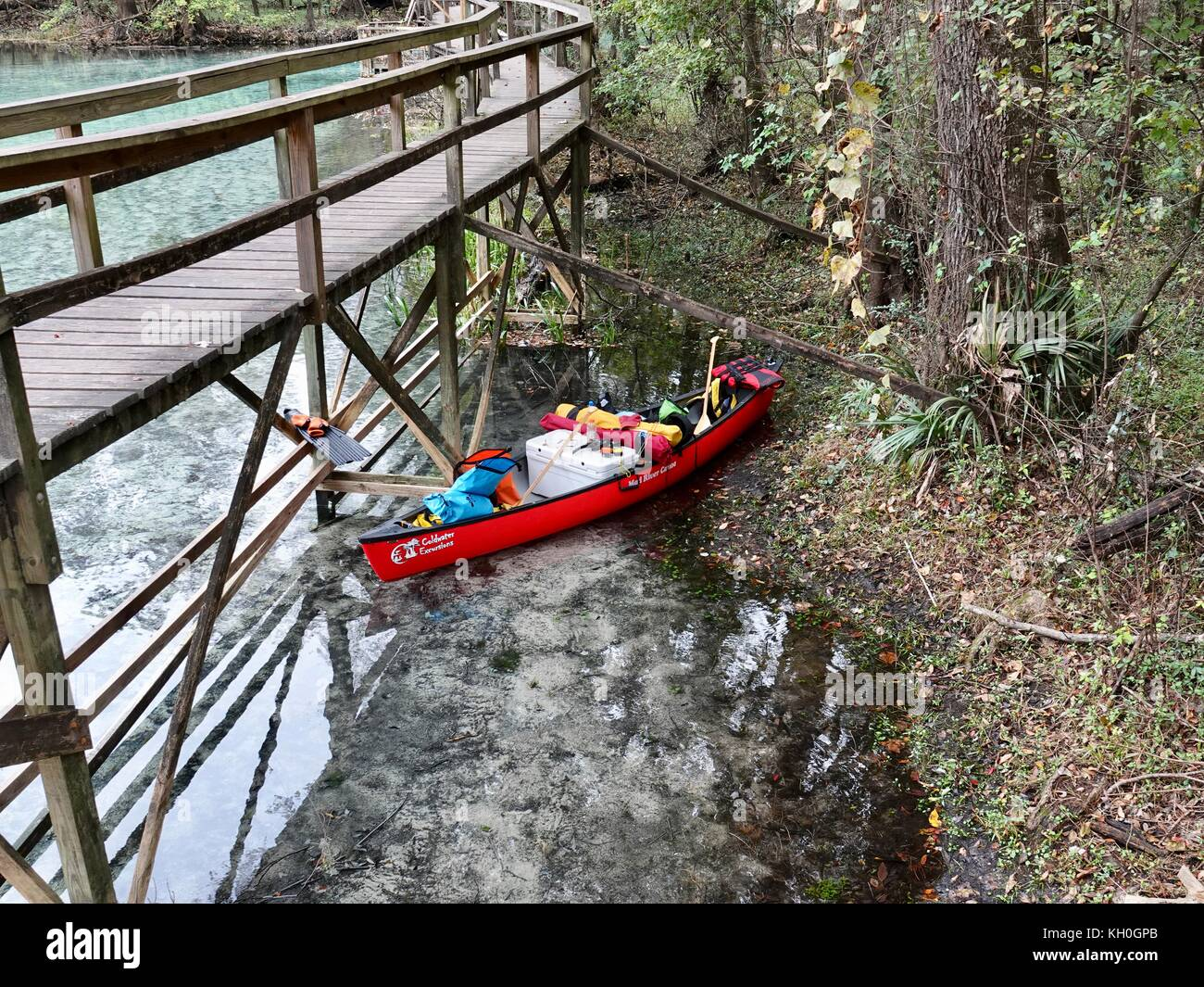 timeless design 0ad13 1c0e8 Canoe with camping gear, under wooden boardwalk while ...