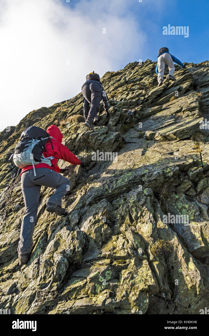 Three hikers scrambling over the arete of Sharp Edge in the Lake District National Park in England. - Stock Image