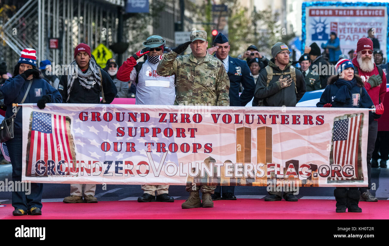 New York, USA, 11 Nov 2017.  Ground Zero Volunteers salute the national anthem before starting their march through - Stock Image