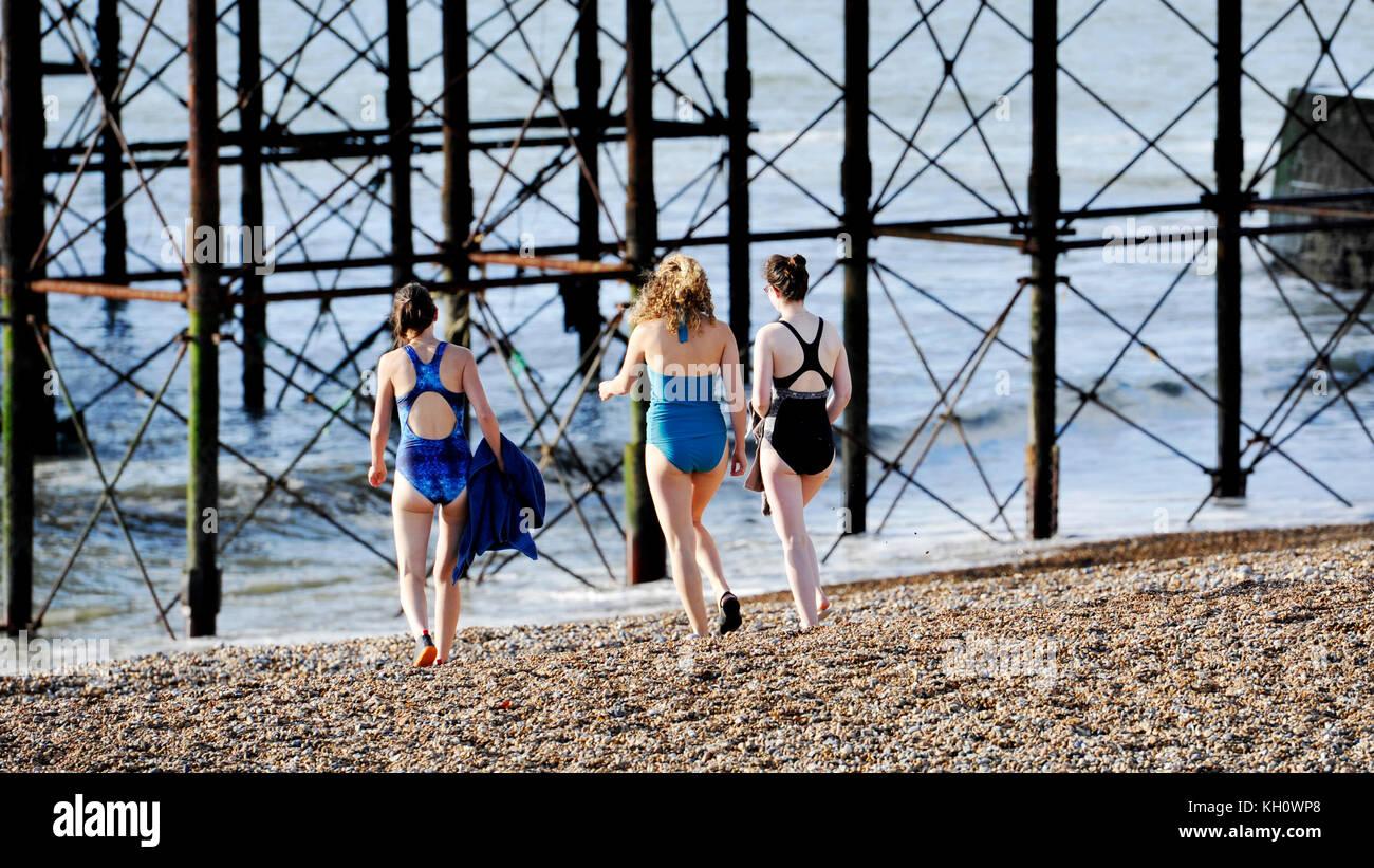 Brighton UK 12th November 2017 - Swimmers head into the sea off Brighton beach today despite the cold but sunny - Stock Image