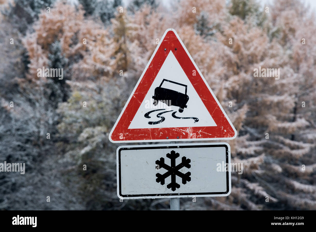 Upper Bavaria, Germany. 13th Nov, 2017. A traffic sign warning of packed snow on the street standing in front of - Stock Image