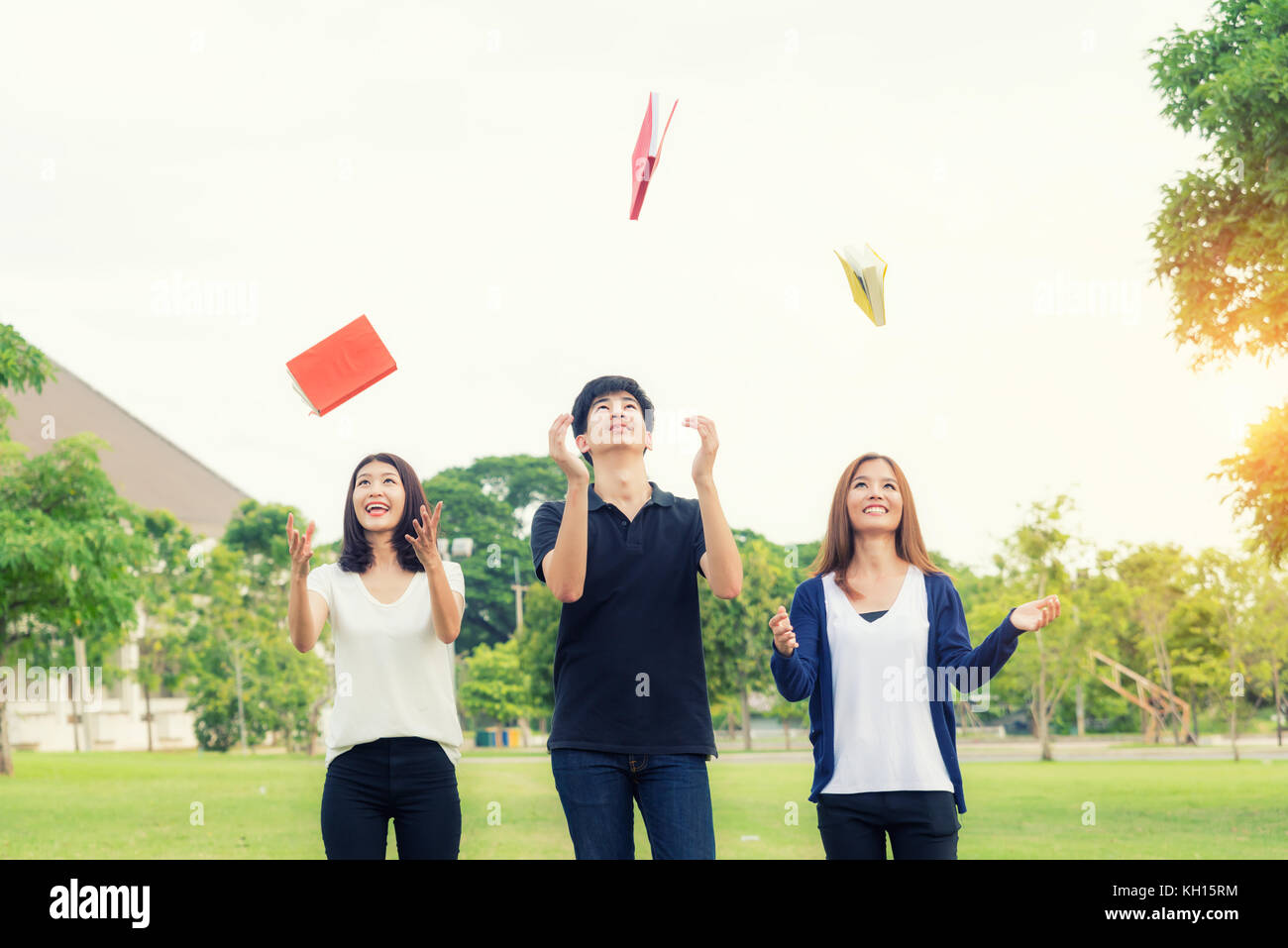 Group of Asian students throw book on air celebrating complete academic year. - Stock Image