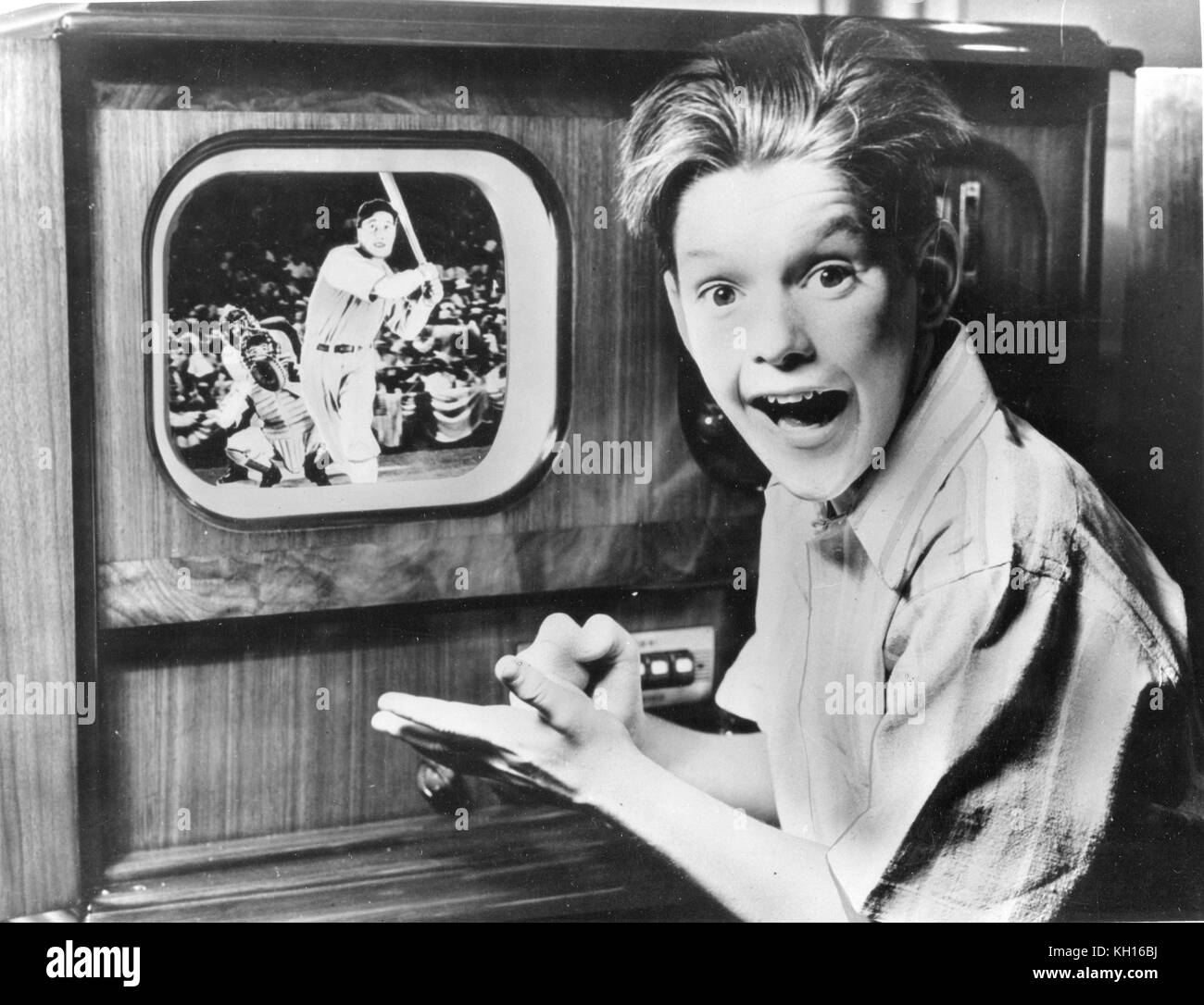 A young boy reacts with excitement while watching a television broadcast of a baseball game on a table model set - Stock Image