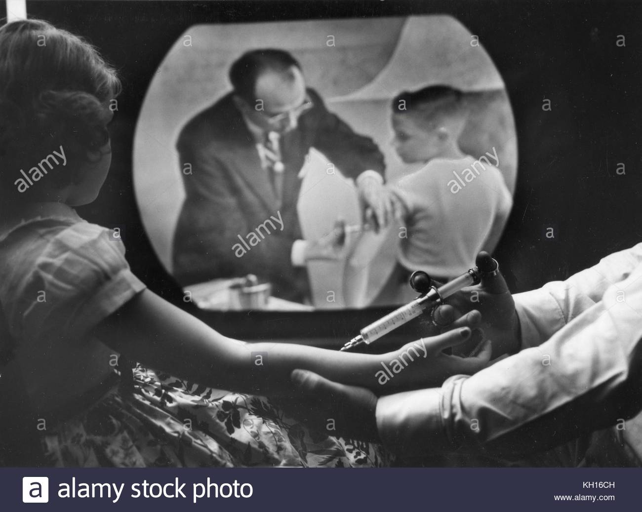 An eight-year-old girl receiving her own polio vaccine watches Dr. Jonas Salk inoculate a boy on closed circuit - Stock Image