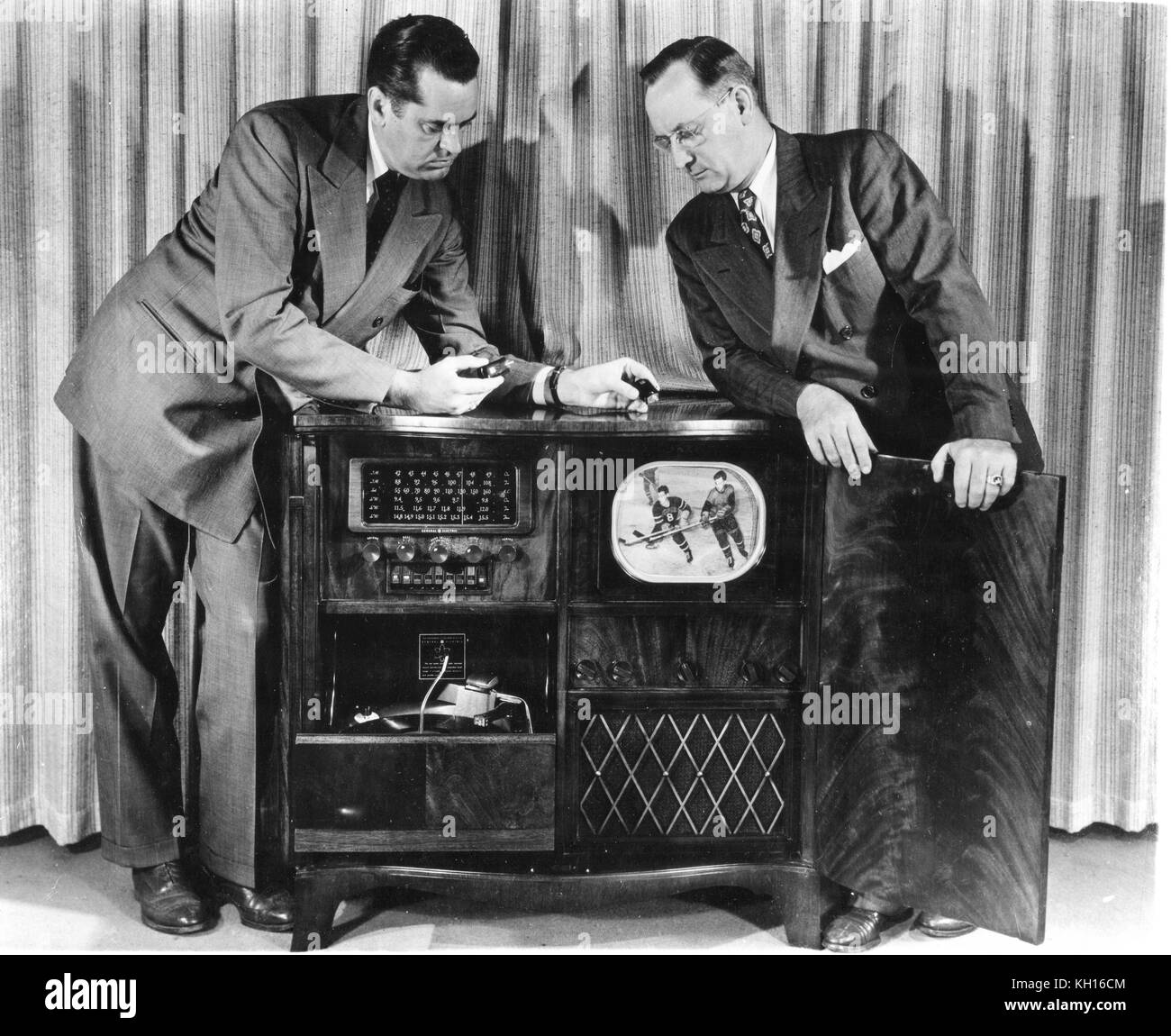 Two men demonstrate the General Electric Model 840 radio-television-phonograph combination, priced at $995, Syracuse, - Stock Image