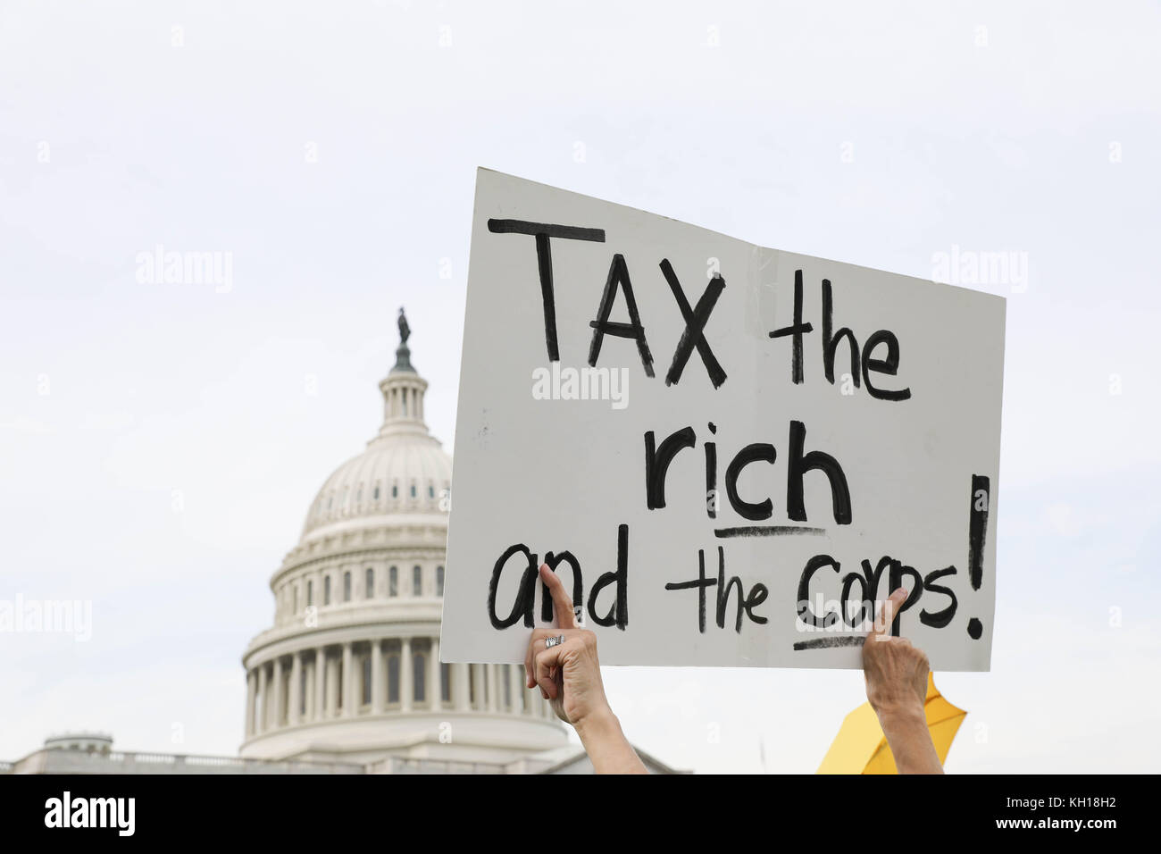 A protestor holds up a sign saying 'Tax the Rich' during a Democratic rally in opposition to the Republican Tax - Stock Image