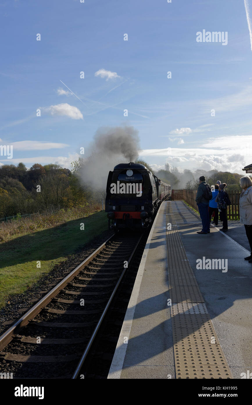 Steam train arriving at platform, passengers waiting behind tactile surface, long shadows, at burrs country park - Stock Image