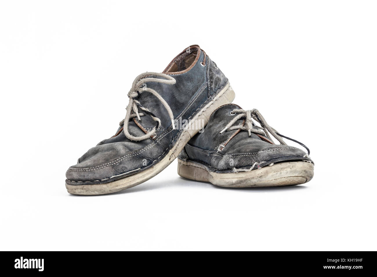 A pair of old worn-out grey leather lace-up shoes against a white background - Stock Image