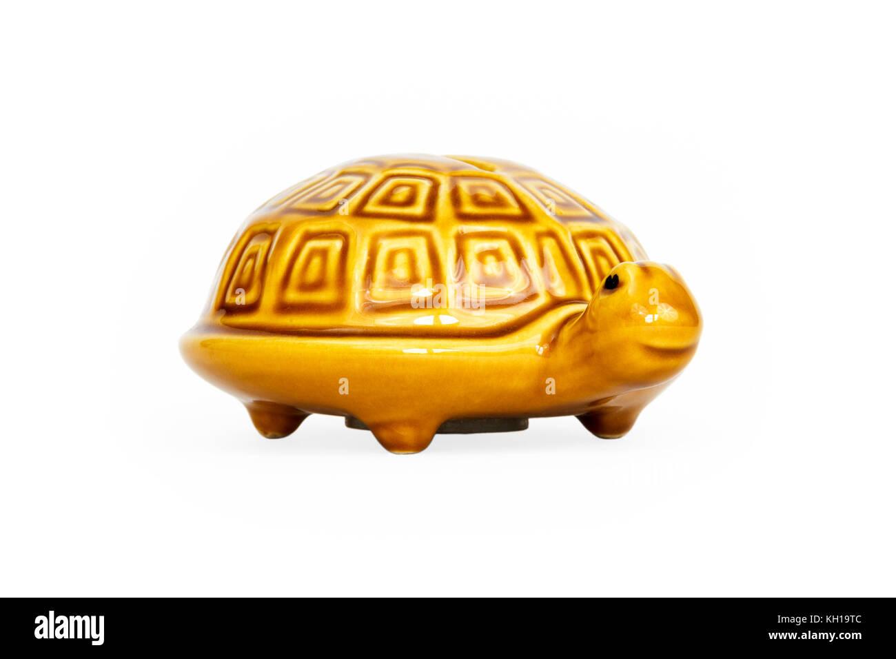 A glazed yellow or orange ceramic tortoise money box, against a white background - Stock Image