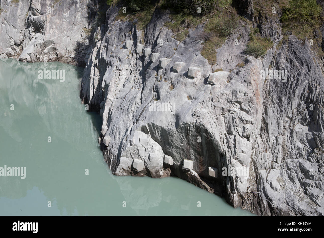 Geologic engineering: Reinforced mountain wall above a lake by using shotcrete and rock bolts as slope stabilization. - Stock Image