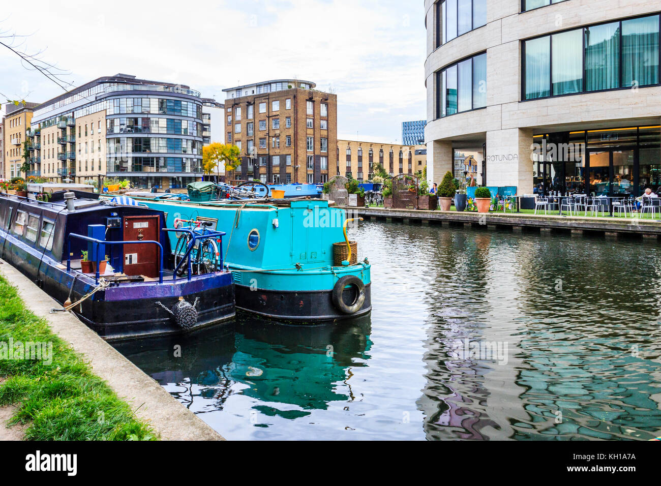 Narrowboats moored at Battlebridge Basin, King's Cross, London, UK, the Rotunda cafe in the King's Place - Stock Image