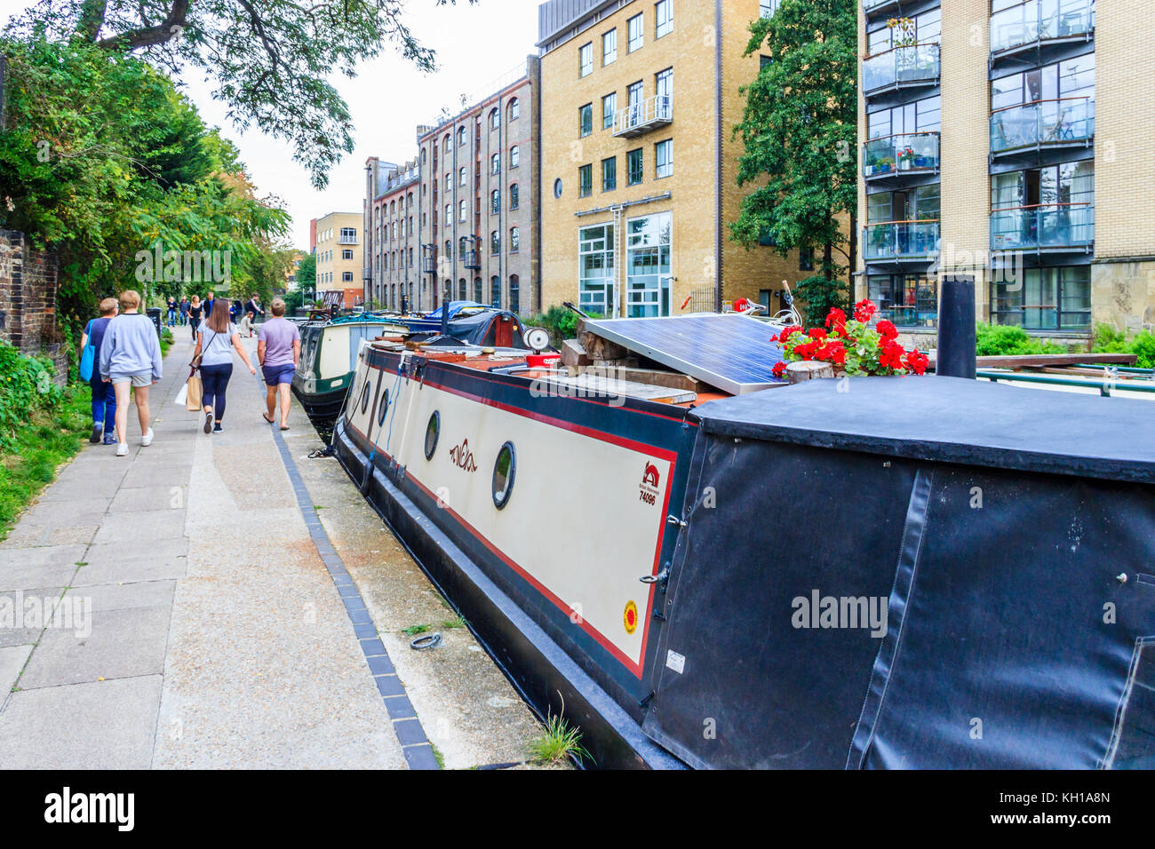 People walking away on the towpath of Regent's Canal past narrowboats moored at Battlebridge Basin, King's Cross, Stock Photo
