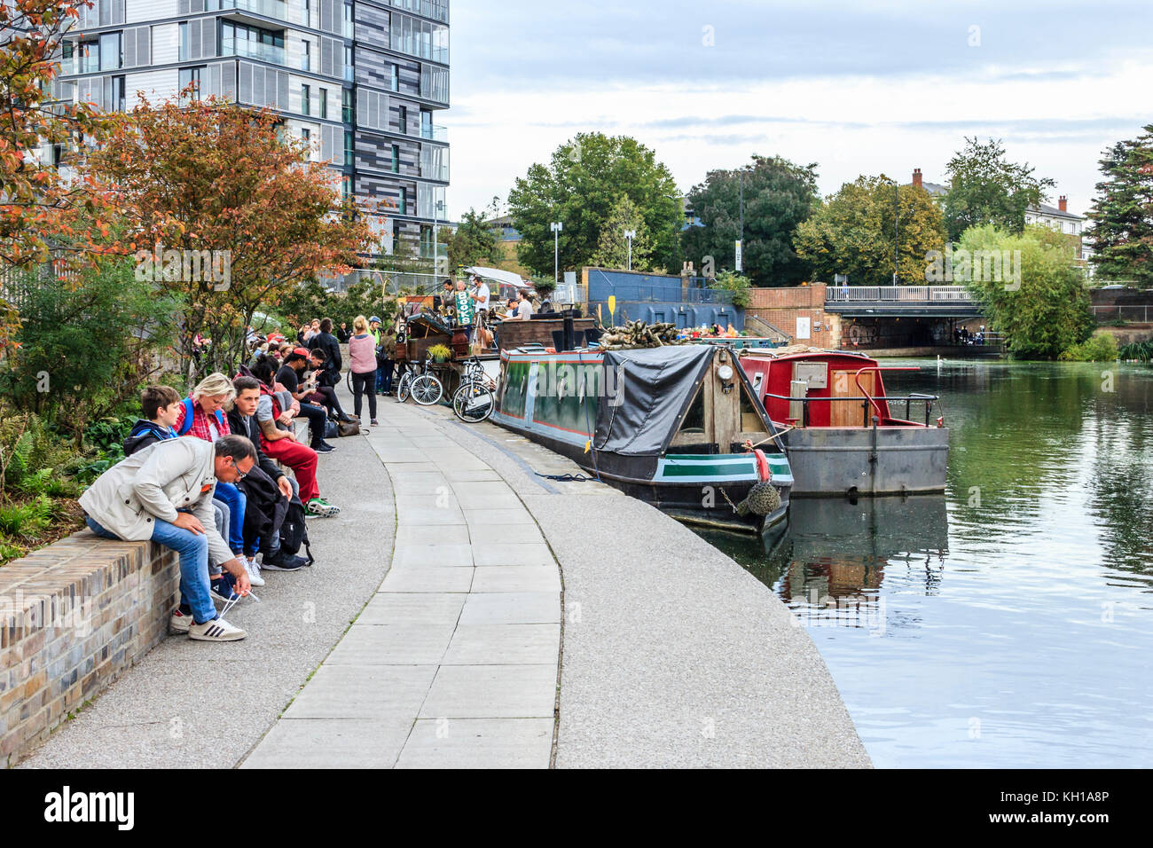 People sitting and congregation on the towpath on Regent's Canal at King's Cross, London, UK, 2017 - Stock Image