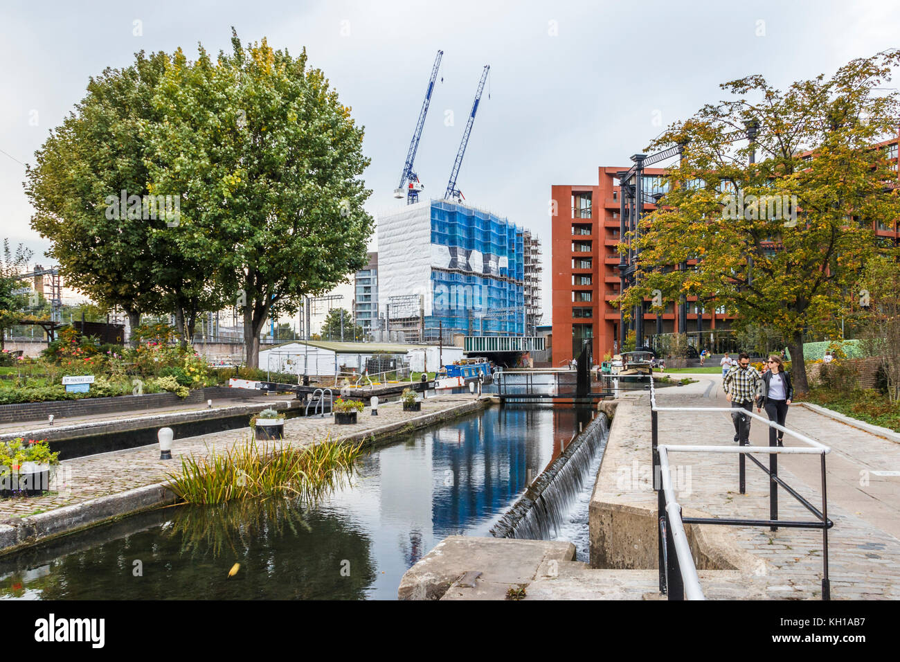 Man and woman strolling on the towpath of Regent's Canal at St. Pancras Lock, Kings Cross, London, UK, construction - Stock Image