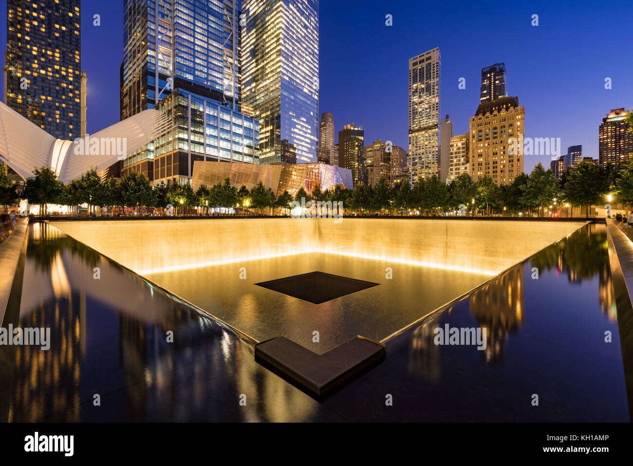 The North Reflecting Pool illuminated at twilight with view of the World Trade Center Tower 3 and 4 and the Oculus. Stock Photo
