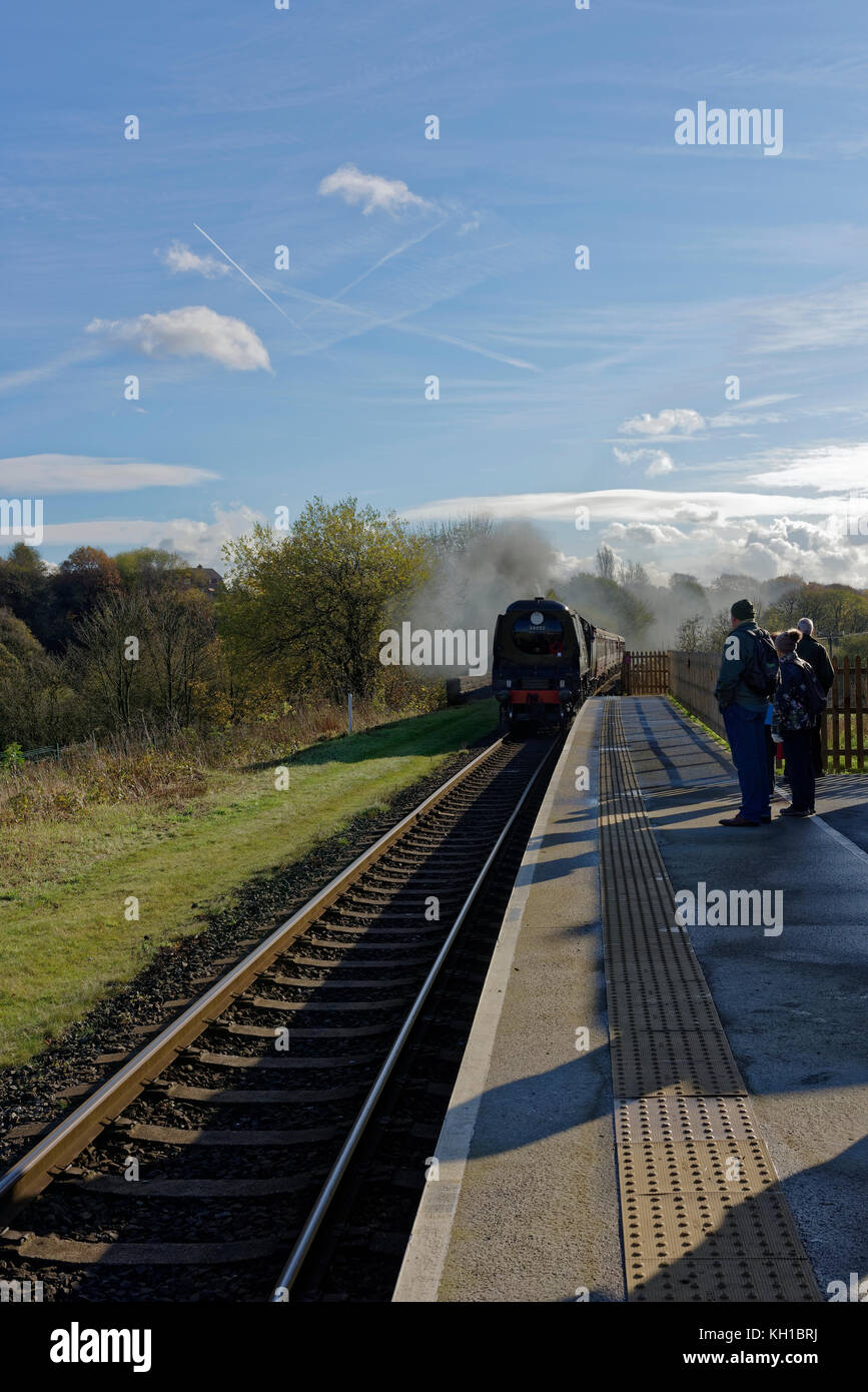 Steam train arriving at platform, passengers waiting behind tactile surface at burrs country park railway station - Stock Image