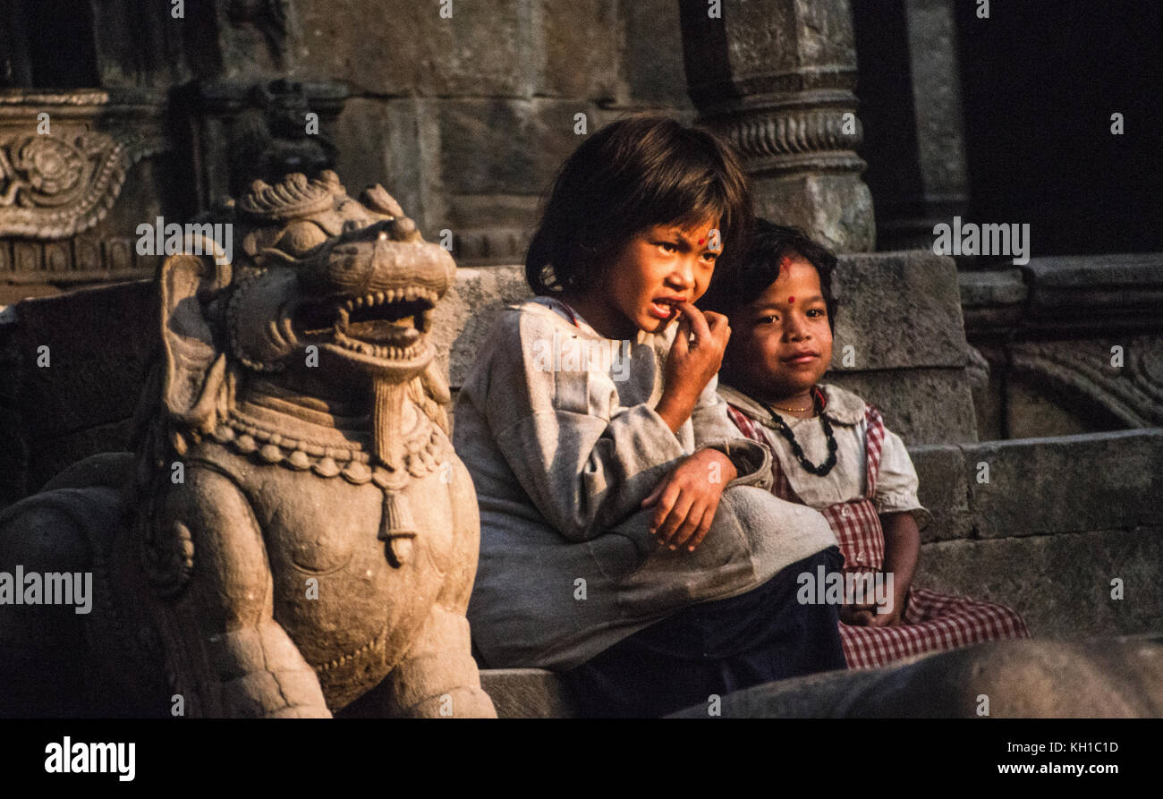 Nepali Girls Sit by Stone Creature - Stock Image