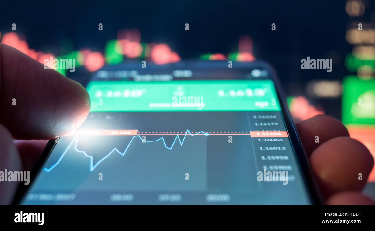 Day trader Forex using mobile phone - Stock Image