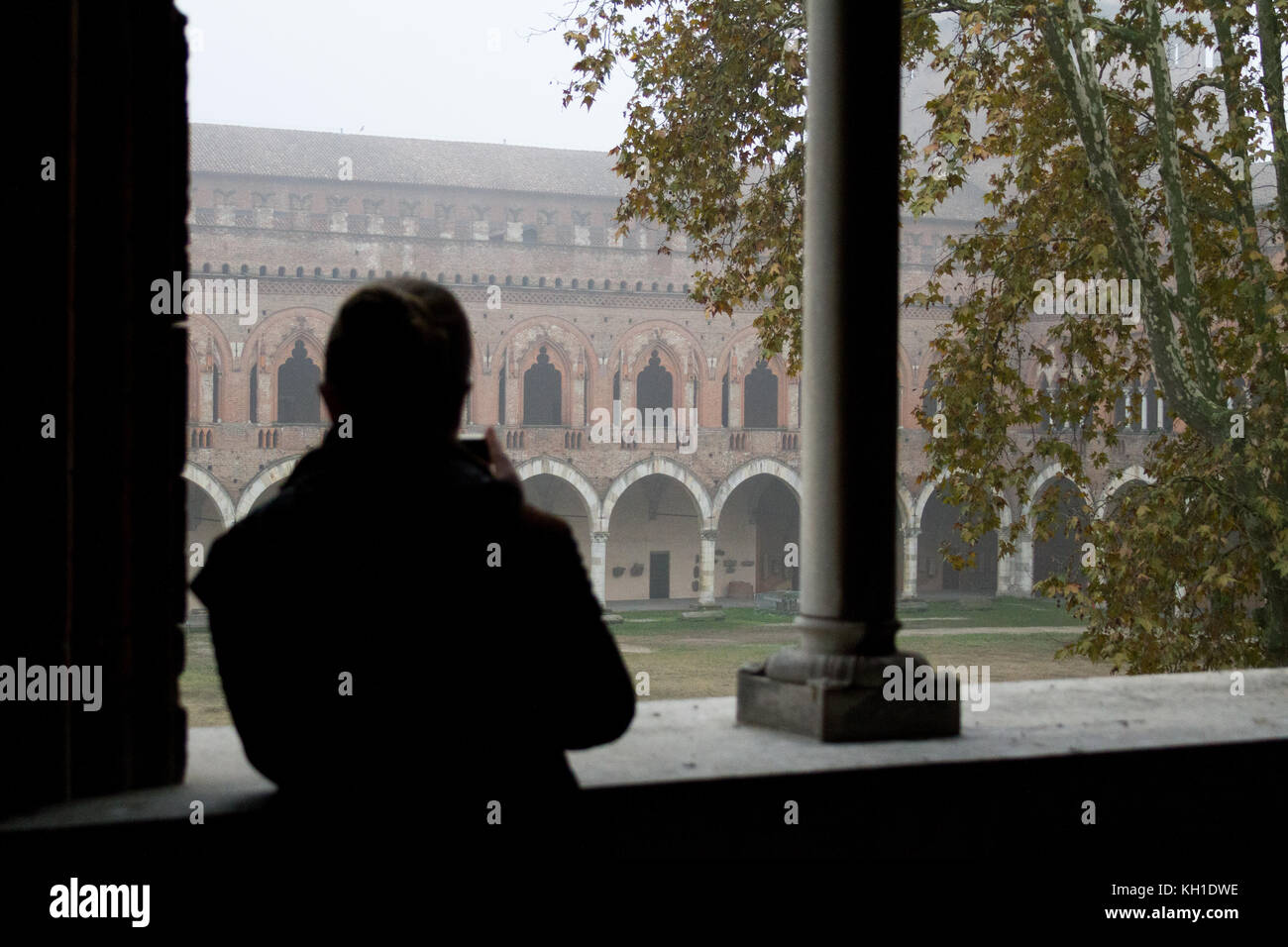 A silhouette of a girl taking a photo of Castello Visconteo through a lucent gothic parapet - Stock Image