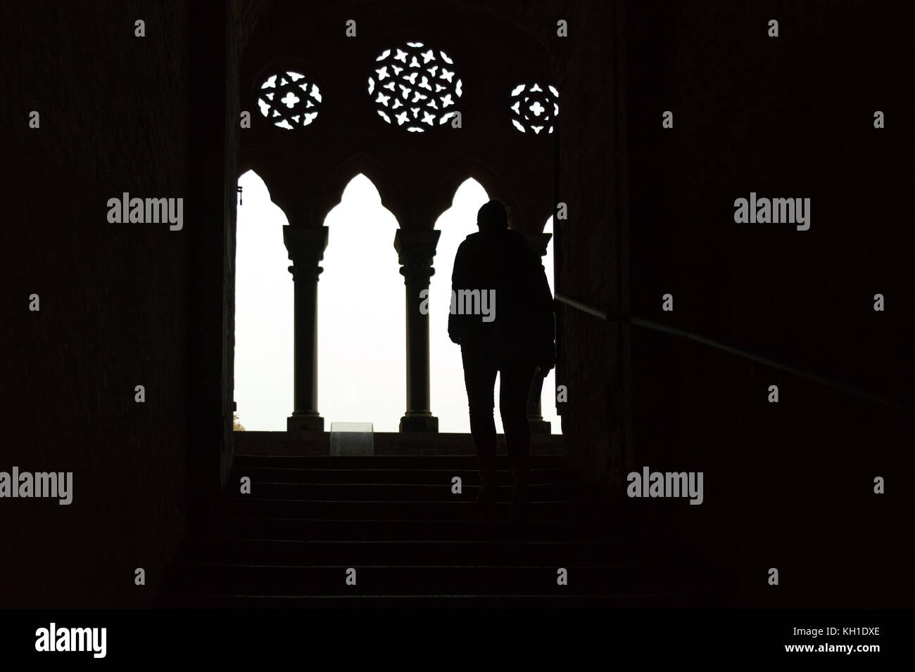 A silhouette of a girl walking up the stairs to a lucent gothic parapet - Stock Image