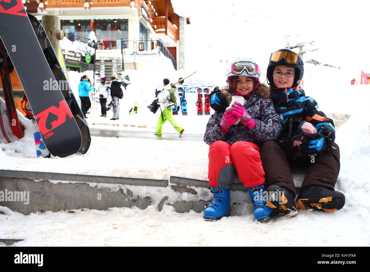 kids in the snow wearing ski suits, helmets and goggles - Stock Image
