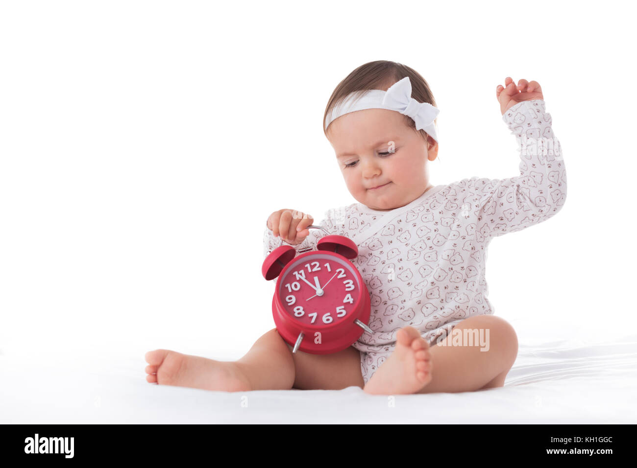 Portrait of cute Baby girl and alarm clock isolated on white background - Stock Image