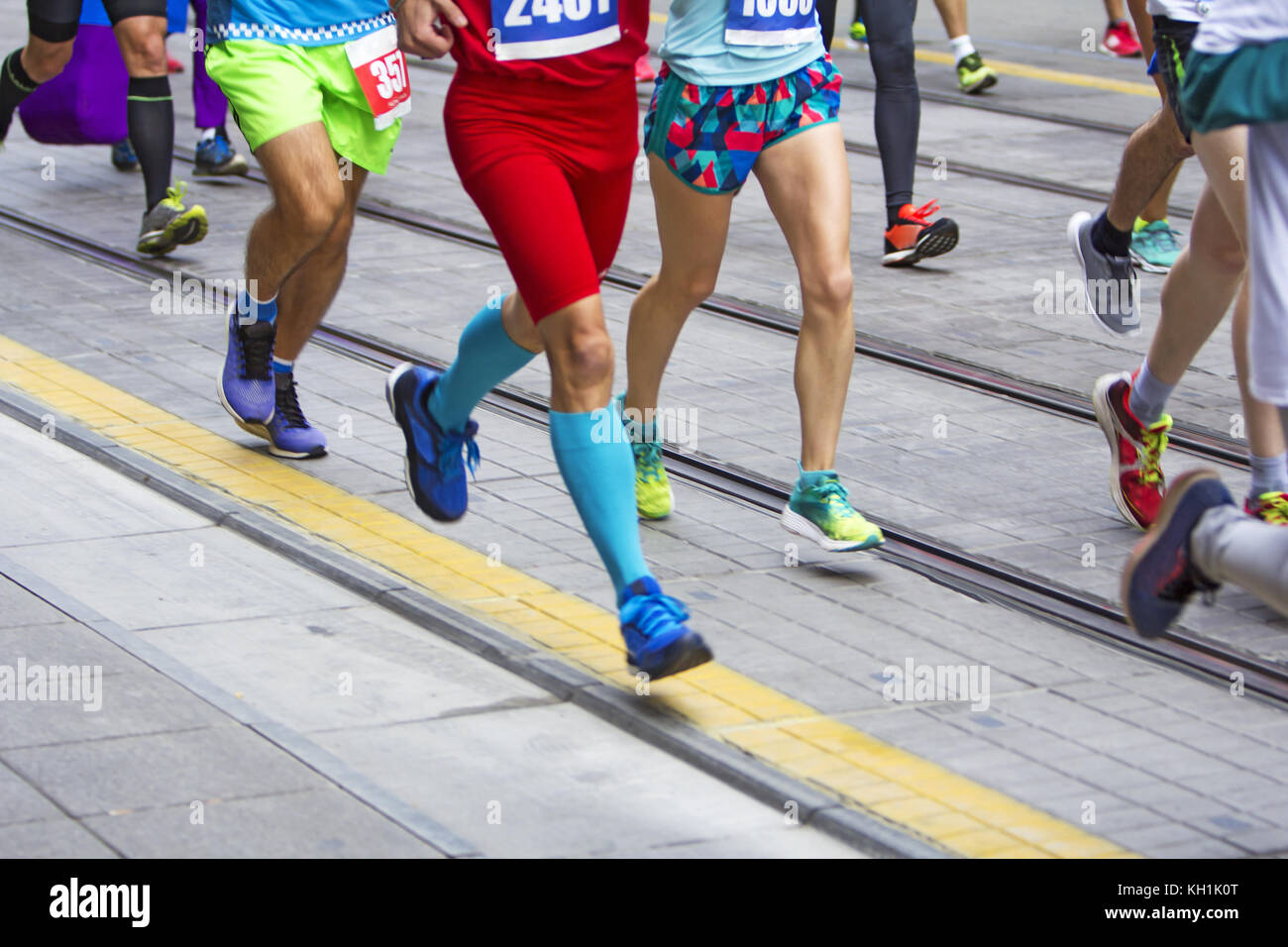Marathon runners race in city streets, blurred motion - Stock Image