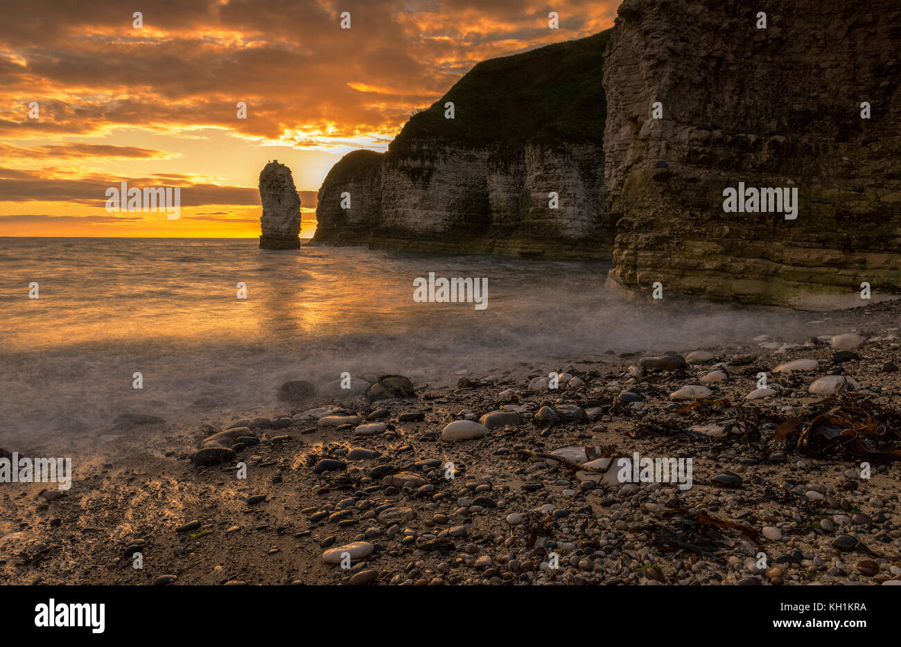 coastal sunrise on a pebble beach - Stock Image
