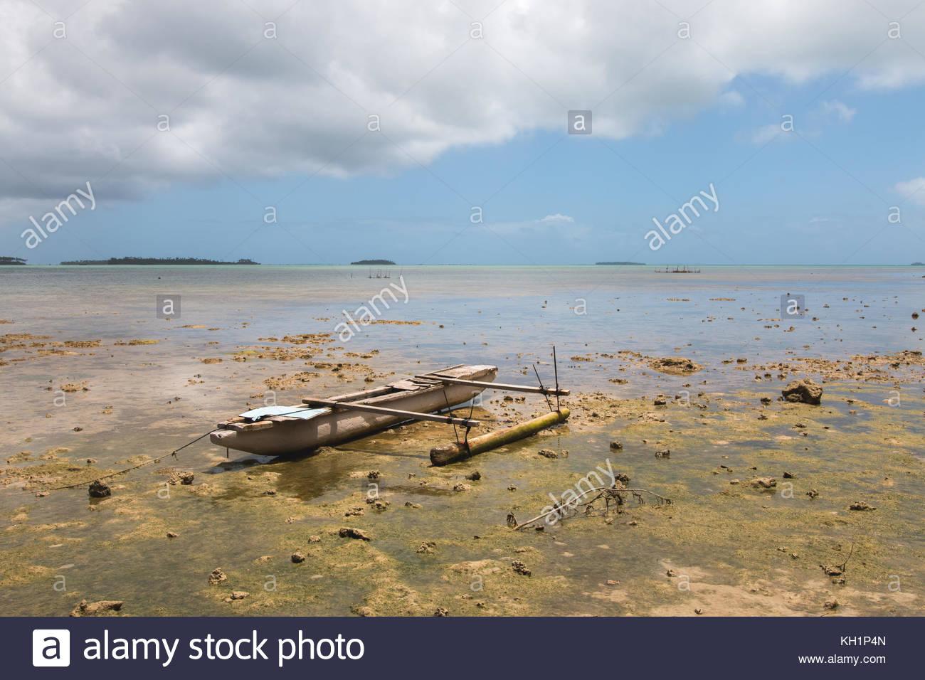 Abandoned old outrigger canoe on shallow water, Tongatapu Island, Tonga - Stock Image